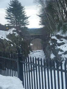 Dark overlook of snow-covered river and stone-bridge--'....the depths of shadows & evil....'